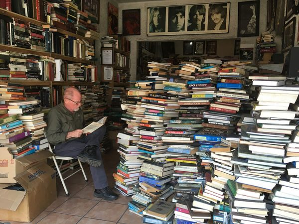 Pic: Man sitting reading in bookstore facing feet-high stacks of books